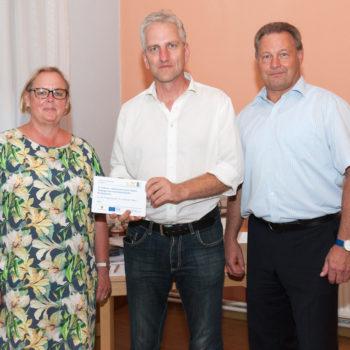 Pfarrer Götz Beyer nimmt die Erinnerungstafel für die Kirchengemeinde St. Andreas Biere entgegen